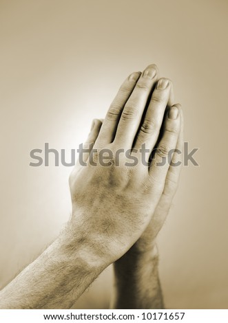 Sepia toned photograph of hand clasped in prayer - stock photo