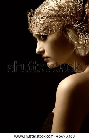 Sepia toned portrait of attractive retro-style girl in bonnet over black - stock photo