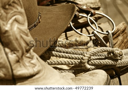 Sepia-toned rustic western image of cowboy boots, cowboy hat, rope, horse bit and stacked wood (mid-focus point). - stock photo