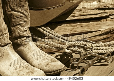 Sepia-toned rustic western image of cowboy boots, cowboy hat, rope, horse bits and stacked wood.