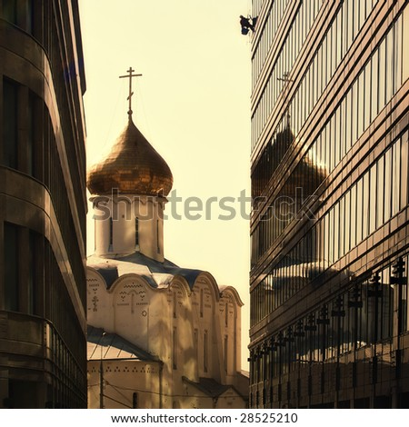 Sepia toned shop of old russian church between two modern skyscrapers. May be used as contrasts concept. - stock photo
