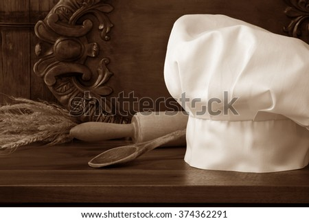 Sepia toned still-life of chef's hat in rustic setting with vintage wooden spoon and rolling pin on wood cutting board.. Decorative, carved serving tray as background. Baking or Cooking concept.