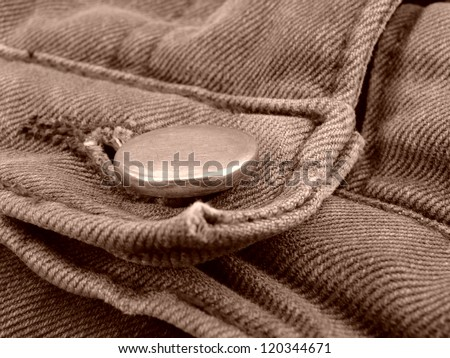 sepia toned worn-out denim fragment with a button
