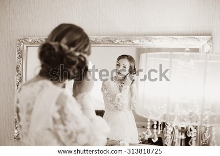 Sepia wedding picture of a bride getting ready in hotel room.  - stock photo