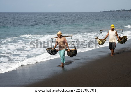 SEPTEMBER 18, 2014 - BALI, INDONESIA: Workers carry bags of sea water to bring inland to saturate the sand to make natural sea salt. Making natural sea salt is a traditional cottage industry here.