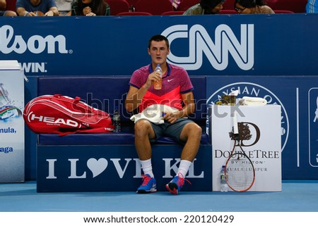SEPTEMBER 23, 2014 - KUALA LUMPUR, MALAYSIA: Bernard Tomic of Australia takes a drink at game break in his match at the Malaysian Open Tennis 2014 event. This is an ATP sanctioned tournament. - stock photo