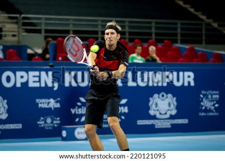 SEPTEMBER 23, 2014 - KUALA LUMPUR, MALAYSIA: Jarkko Nieminen of Finland makes a backhand return in his first round match at the Malaysian Open Tennis 2014 event. This is an ATP sanctioned tournament. - stock photo