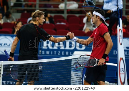 SEPTEMBER 25, 2014 - KUALA LUMPUR, MALAYSIA: Leonardo Mayer congratulates Jarkko Nieminen for his win in their match at the Malaysian Open Tennis 2014. This is an ATP sanctioned tournament. - stock photo