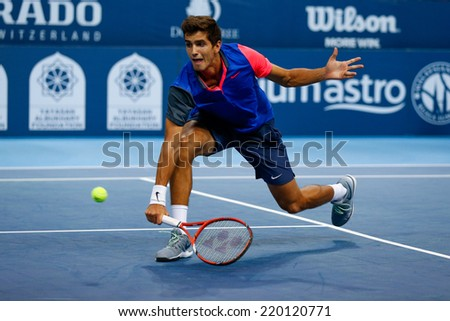 SEPTEMBER 23, 2014 - KUALA LUMPUR, MALAYSIA: Pierre-Hugues Herbert of France makes a backhand volley in his first round match at the Malaysian Open Tennis 2014. This is an ATP sanctioned tournament. - stock photo