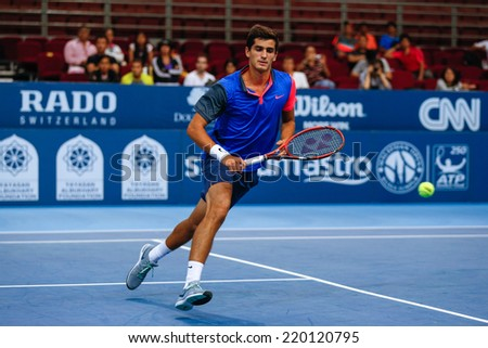 SEPTEMBER 23, 2014 - KUALA LUMPUR, MALAYSIA: Pierre-Hugues Herbert of France watches the ball fly out in his first round match at the Malaysian Open Tennis 2014. This is an ATP sanctioned tournament. - stock photo