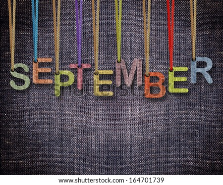 September letters hanging strings with blue sackcloth background. - stock photo