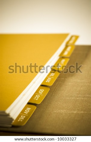 September & October - Object shot of a modern Agenda Planner Book. Selective focus shot with intentional slight gold toning and vignetting to enhance mood. - stock photo