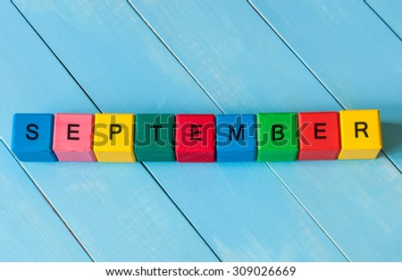 September sign on color wooden cubes with light blue wood background. Back to school time. - stock photo