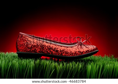 Sequined red slipper on green grass against a fading red background - stock photo