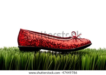 Sequined red slipper on green grass on white - stock photo