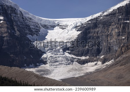 Seracs of ice and snow tumble onto the Dome Glacier from the Columbia Ice Field near the top of Snow Dome mountain. - stock photo