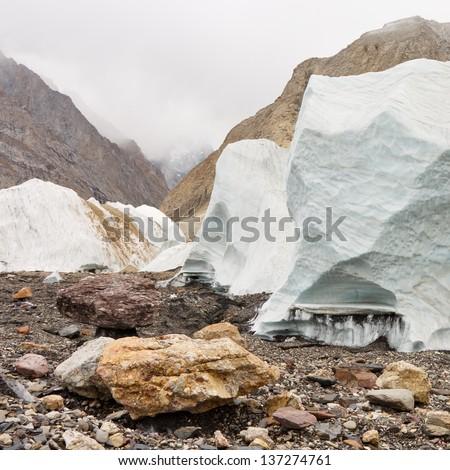 Seracs rising from the scree-covered Baltoro Glacier, Karakorum, Pakistan - stock photo
