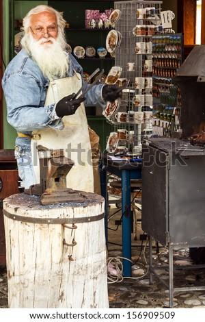 Serbian blacksmith men in souvenir shop in Cetinje, Montenegro.  - stock photo