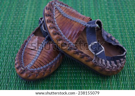 Serbian peasant shoe on green tablecloth - stock photo