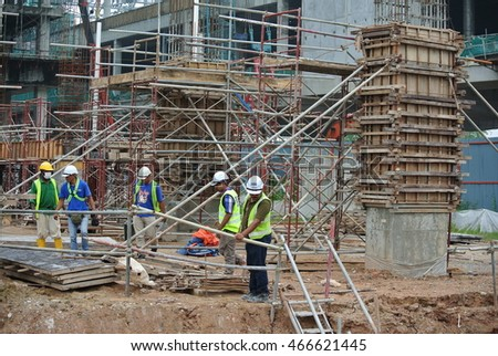 SEREMBAN, MALAYSIA -JULY 01, 2016: Construction workers working at the construction site at Malacca, Malaysia during daytime. They are wearing proper safety gear to ensure they are safe working.