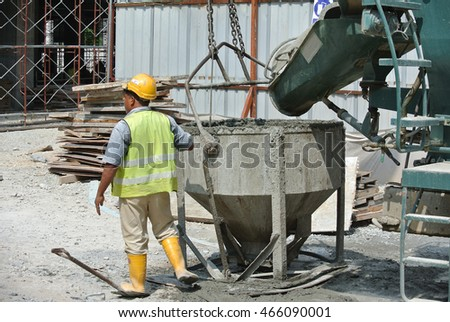 SEREMBAN, MALAYSIA -JUNE 06, 2016: Concrete mixer lorry pouring wet concrete into concrete bucket at the construction site.