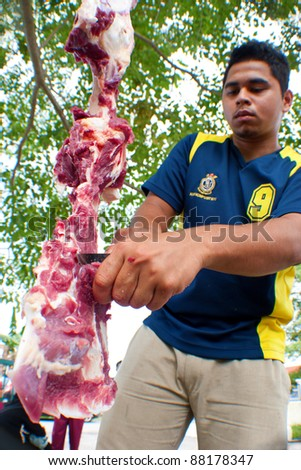 SEREMBAN, MALAYSIA - NOV 6: An unidentified Malaysian Muslim prepares meat to distribute to the poor and homeless during Eid Al-Adha Al Mubarak, the Feast of Sacrifice on November 6, 2011 in Seremban, Malaysia. - stock photo
