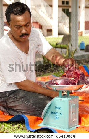SEREMBAN - NOVEMBER 17: A Malaysian Muslim preparing meat to distribute to the poor and homeless during Eid Al-Adha Al Mubarak, the Feast of Sacrifice November 17, 2010 in Seremban, Malaysia. - stock photo
