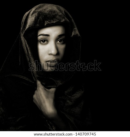 Serene African American woman wearing a shawl in monochrome with sepia toning isolated on black - stock photo