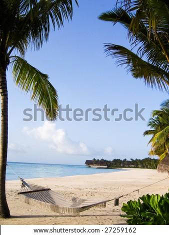 Serene beach with peaceful sea and a hammock among palm trees - stock photo