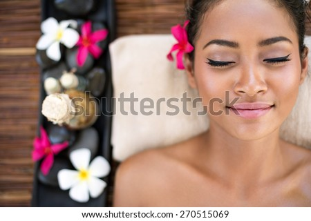 Serene beautiful spa woman relaxing on massage desk  - stock photo