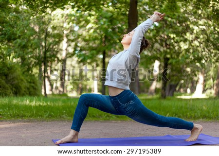 Serene beautiful sporty young woman working out on blue mat on the street in park alley, doing high lunge exercise, virabhadrasana 1, warrior 1 posture, surya namaskar complex, full length - stock photo