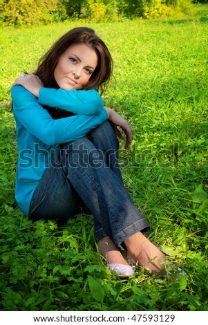 Serene beautiful young woman resting on green grass - stock photo