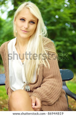 Serene beauty, an enigmatic sexy young blonde model sits on a park bench in a tan jersey. - stock photo