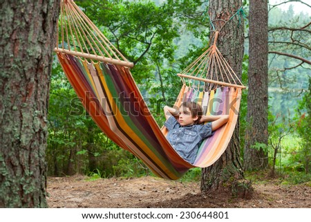 Serene boy lying in striped hammock in summer forest - stock photo