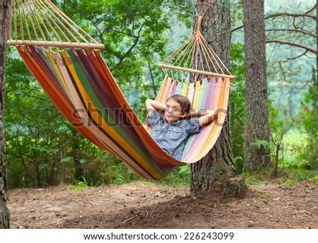 Serene boy lying in striped hammock outdoors - stock photo