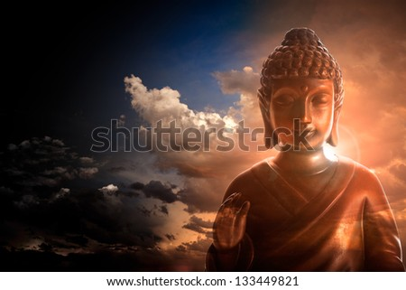 Serene Buddha statue on stormy and cloudy background - stock photo