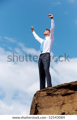 Serene businessman standing on the top of mount with his arms raised to the sky