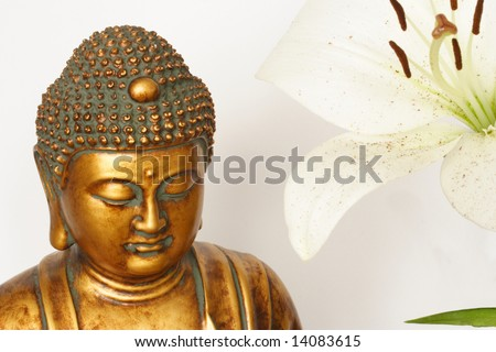 Serene bust of Buddha and Madonna lily - stock photo
