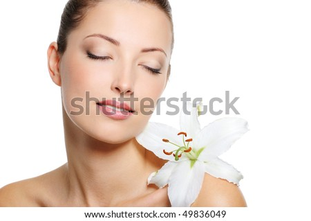 Serene face of a beauty fresh woman with closed eyes and flowe on her shoulder - stock photo