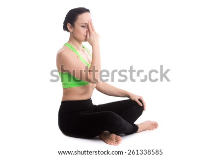 Serene girl practicing yoga nadi shodhana pranayama (Alternate Nostril Breathing), sitting in Easy (Decent, Pleasant Pose), Sukhasana, meditation, copy space - stock photo
