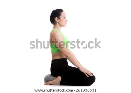 Serene girl practicing yoga, Sitting on pillow in Virasana, Hero Pose, asana for legs, meditation, pranayama, breathing, relieving stress, copy space - stock photo