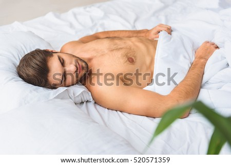 Serene guy having nap in bed