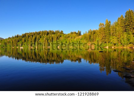 Serene lake in Utah with beautiful reflection of the mountain and trees. - stock photo