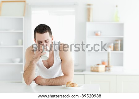 Serene man having breakfast in his kitchen