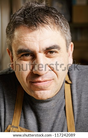 Serene middle-aged caucasian man in apron and gray sweater - stock photo