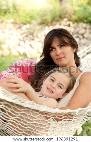 Serene mother and young daughter relaxing together on a hammock in a holiday home garden with green grass during a sunny summer day. Family activities and lifestyle outdoors. - stock photo