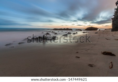 Serene night beach seascape. This is an image of a serene beach taken at night with orange/red coloring on the horizon and dramatic clouds above.  This image was taken in Laguna Beach California. - stock photo