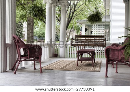 Serene old fashioned porch with wicker furniture in spring. - stock photo