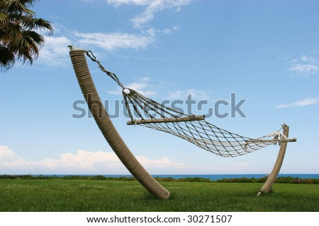 Serene place with empty hammock on grassland under blue sky - stock photo