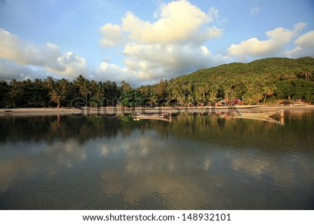 serene reflections of sky and landscape on a beautiful tropical island bay, Thailand - stock photo